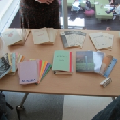 Nine decades of Aurora Literary Journal on a table for guests to look at.